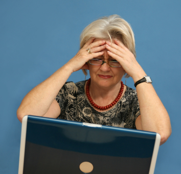 Woman w laptop holding head.jpg